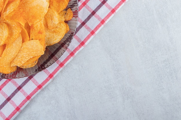 Glass plate of spicy chips placed on stone.