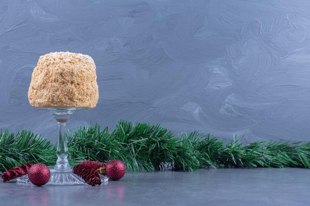 Una lastra di vetro con una deliziosa torta e palline di natale