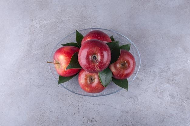 Стеклянная тарелка с блестящими красными яблоками на каменной поверхности.