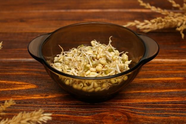 나무 배경 클로즈업에 녹두의 확된 곡물과 유리 접시.