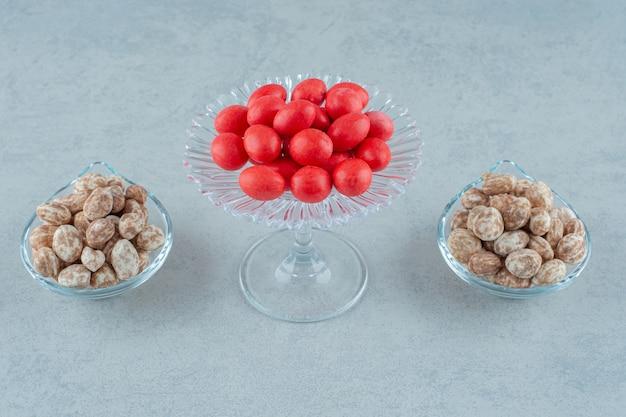 Piatti di vetro pieni di delizioso pan di zenzero e caramelle rosse dolci su superficie bianca