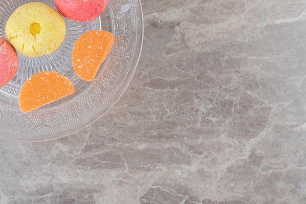 大理石の表面にクッキーとゼリーのお菓子が付いたガラスの盛り合わせ