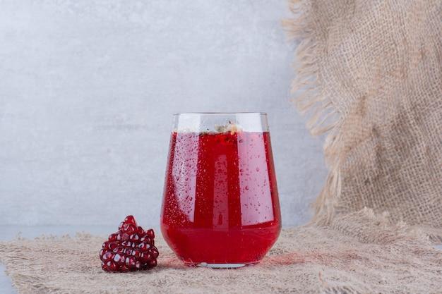 Un bicchiere di succo di melograno su tela con semi.