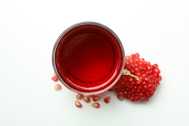 Glass of pomegranate juice and ingredient on white background