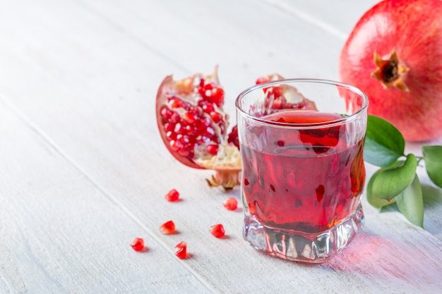 Glass of pomegranate juice and ripe pomegranate on a white wooden background. healthy drink concept. ãâ¡opy space