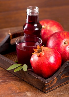 Glass of pomegranate juice on a wooden background.