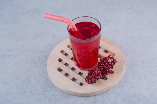 Un bicchiere di succo di melograno su un pezzo di legno con paglia. foto di alta qualità