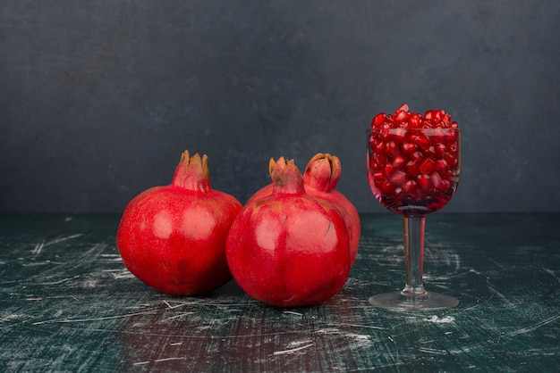 Glass of pomegranate seeds and pomegranate on marble surface.