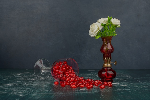 Glass of pomegranate seeds and white flowers in vase.
