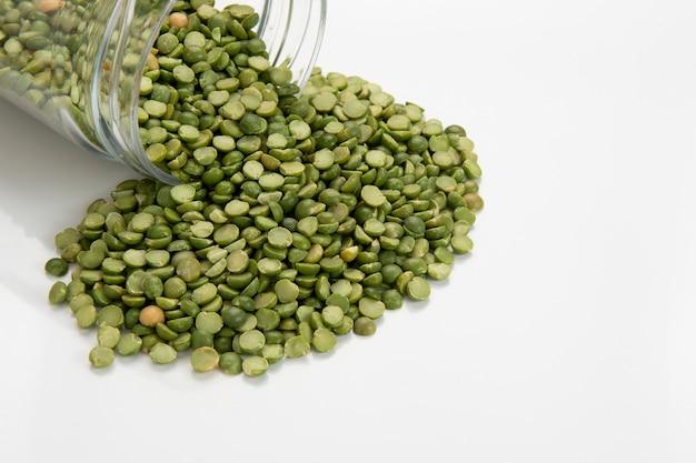 白い背景に注ぐ半分の乾燥エンドウ豆とガラス鍋