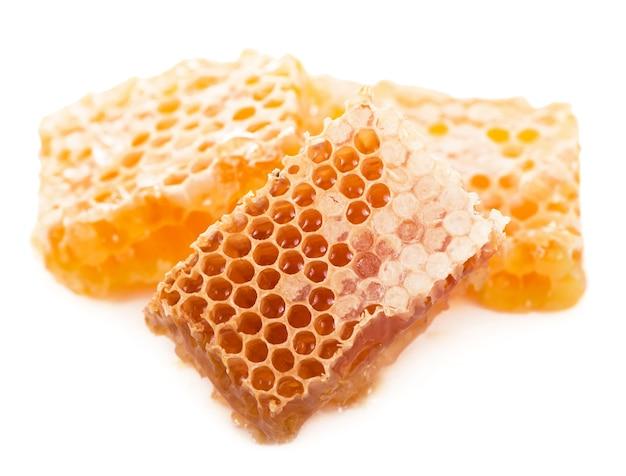 Стеклянный горшок с цветочным медом на белом фоне.