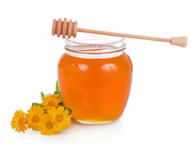 Стеклянный горшок с цветочным медом на белой поверхности