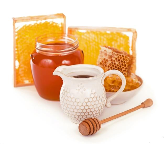 Стеклянный горшок с цветочным медом на белой поверхности Premium Фотографии