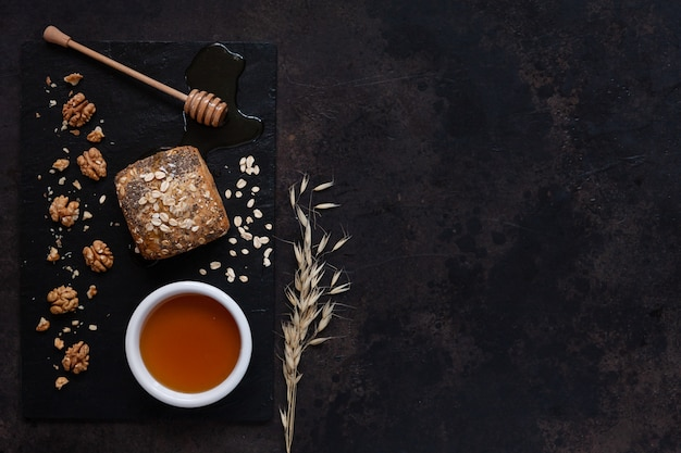 Glass pot with fresh natural honey, bread and walnuts on a stone board.