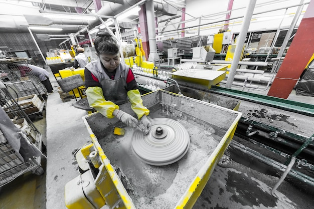 Glass production worker working with industry equipment on factory background