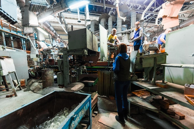 Glass production worker working with industry equipment on factory
