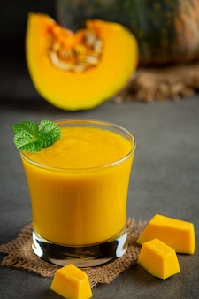 A glass of pumpkin juice and chopped raw pumpkins place on dark floor