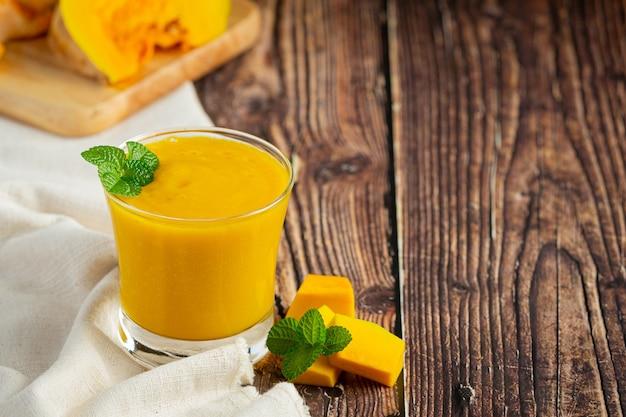 Un bicchiere di succo di zucca e zucche crude tritate posto sul pavimento di legno