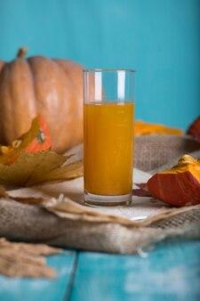 Glass of pumpkin juice on wooden surface. closeup
