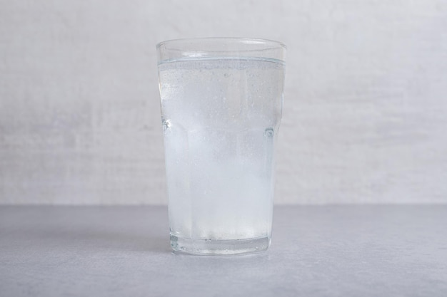 A glass of pure cold water on gray background.
