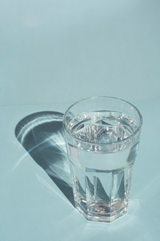 A glass of pure water under sunlight with deep stylish shadows on blue  copyspace
