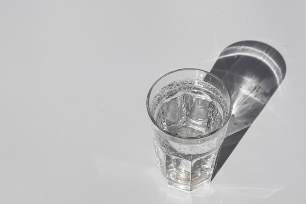 A glass of pure water under sunlight with deep stylish shadows copyspace