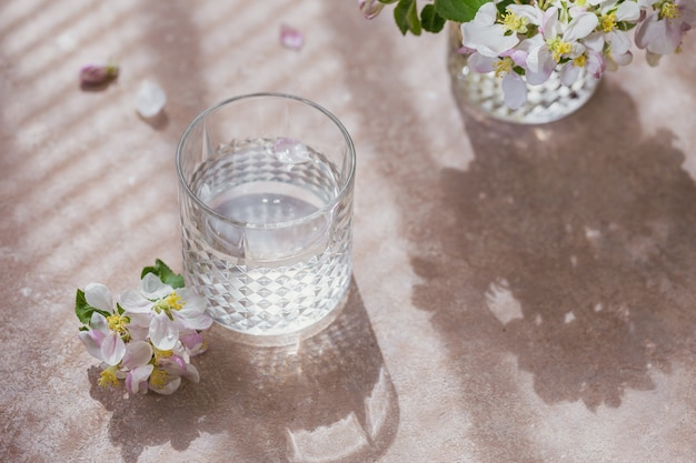 Glass of pure water on the table with blossoming apple tree branch in a glass. morning sunshine mood