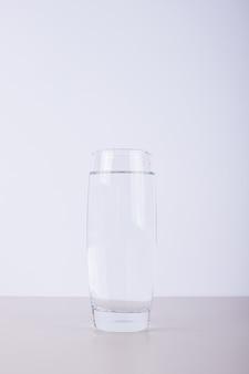 Bicchiere di acqua pura su bianco.