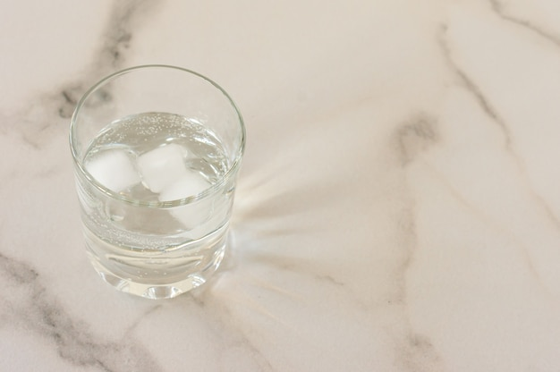 A glass of purified fresh drinking water on a marble table. copy space for text.