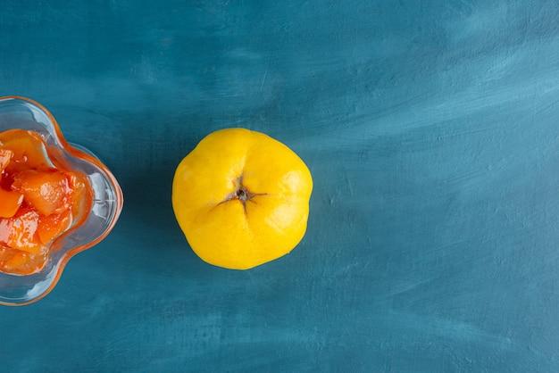 Bicchiere di marmellata di mele cotogne e frutta mela cotogna sulla superficie blu.
