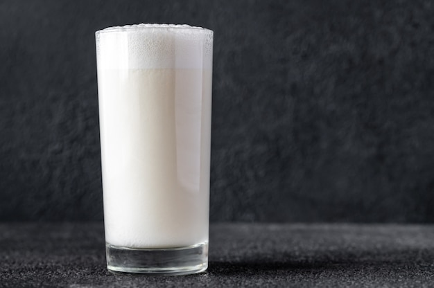 Glass of ramos gin fizz cocktail on dark surface