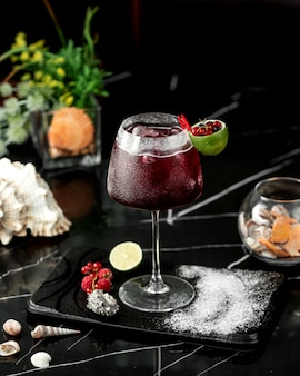 A glass of red cocktail garnished with lime zest and cranberries