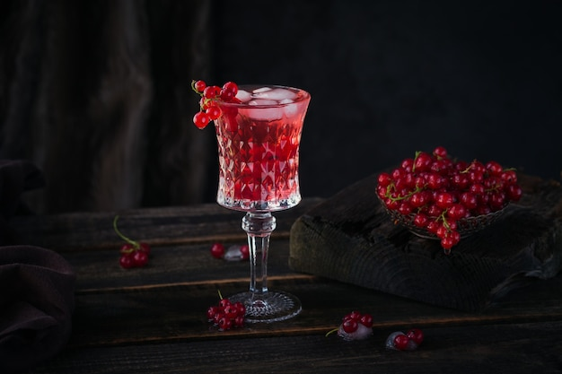 Glass of red currant cocktail or mocktail, refreshing summer drink with crushed ice and sparkling water on a dark wooden