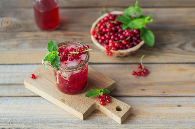 Glass of red currant cocktail or mocktail, refreshing summer drink with crushed ice and sparkling water on a wooden.