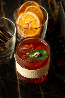 Glass of red drink with ice garnished with leave and rose bud