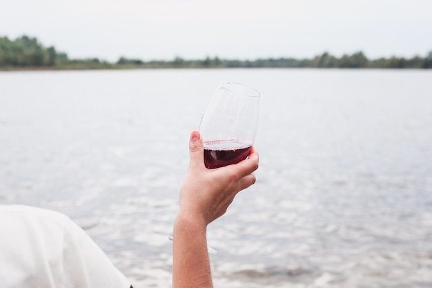 Glass of red dry wine in hand