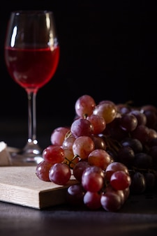 Glass of red fruit wine. close-up of grape vine on a dark