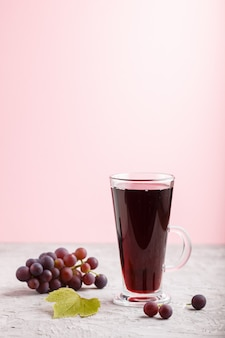 Glass of red grape juice. side view