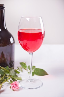 Glass of red grape wine with bottle and roses on the background. romantic dinner concept.