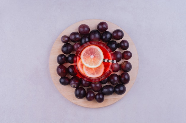A glass of red juice with cherry berries on a wooden board