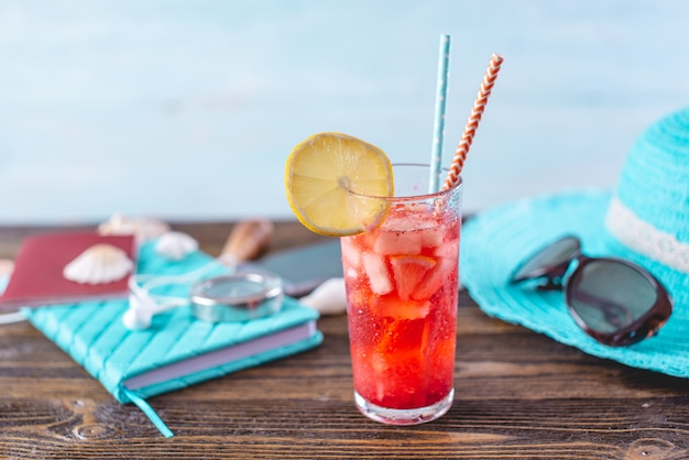 Glass of red lemonade drink with lemon and fruit and straw on the table