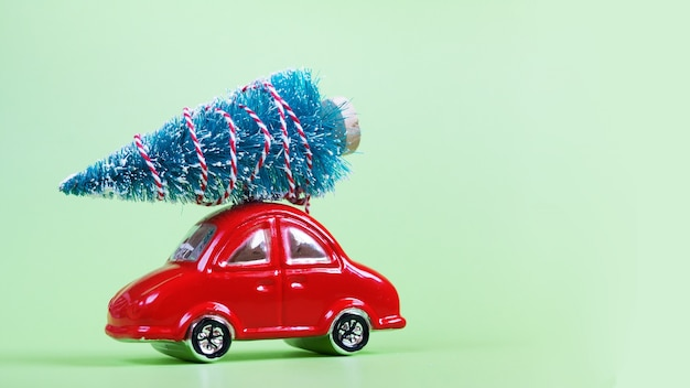 Glass red toy car with christmas decoration on green background