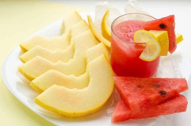 Glass of red watermelon smoothie and slices of melon and watermelon