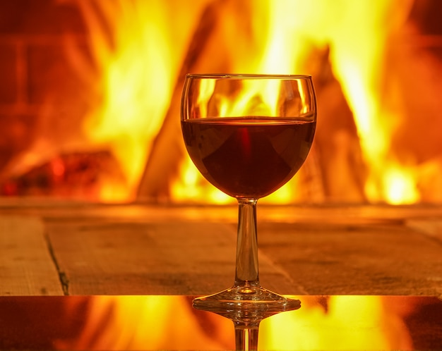Glass of red wine against cozy fireplace