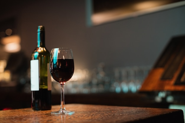 Glass of red wine and bottle on bar counter
