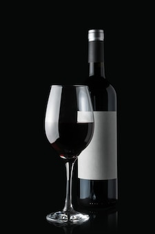 Glass of red wine next to a bottle isolated on black wall