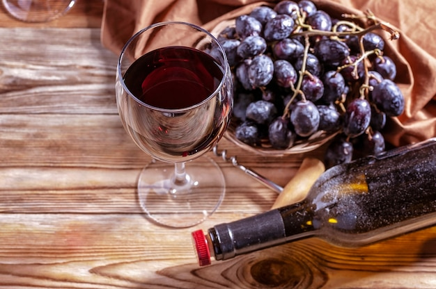 Glass of red wine, bottle and red grapes on a wooden table.