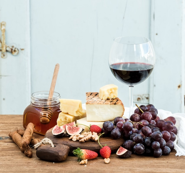 Glass of red wine, cheese board, grapes,fig, strawberries, honey and bread sticks  on rustic wooden table, blue