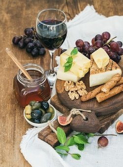 Glass of red wine, cheese board, grapes,fig, strawberries, honey and bread sticks  on rustic wooden table