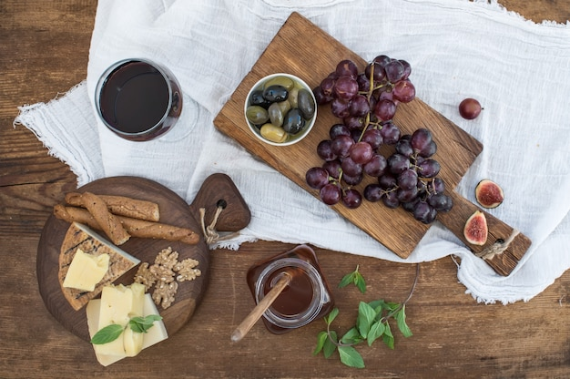 Glass of red wine, cheese board, grapes, walnuts, olives, honey and bread sticks on rustic wooden table